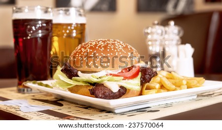Burger, fries and beer in a rustic pub or tavern - stock photo