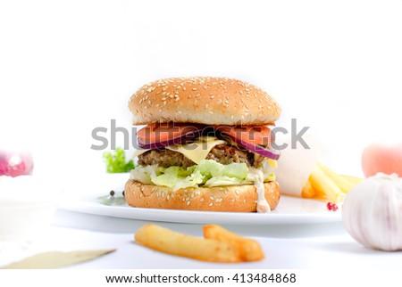 Burger full face with vegetables, spices and fries. Meat hamburger. Hamburger with knife. Beef hamburger. Organic hamburger - stock photo