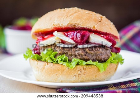 Burger, hamburger sandwich with cutlet of minced meat, cheese brie, camembert, berry cherry sauce - stock photo