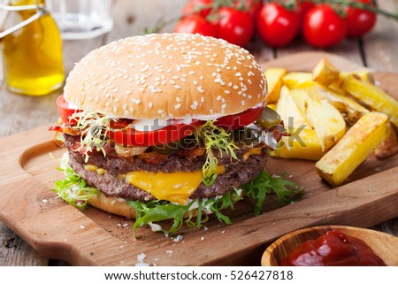 Burger, hamburger with french fries, ketchup, mustard and fresh vegetables on a wooden background