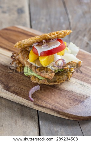 Burger made of asian Ramen noodles with chicken mango tomato cheese red onions and avocado creme on a rustic wooden table - stock photo