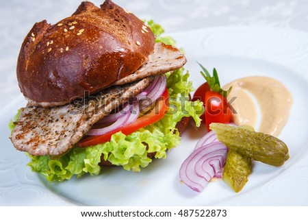 burger made of black bread with salate, cucumber and tomato