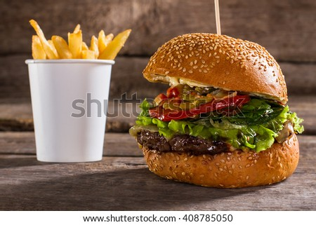 Burger on stick and fries. Delicious burger on wooden background. High-calorie dish in cafe. Fresh lettuce and juicy meat. - stock photo
