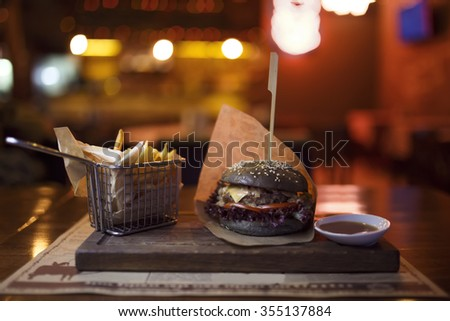 Burger on the table together with potatoes and sauce. blurred background - stock photo