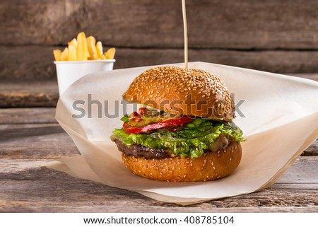 Burger on wax paper. Beef burger on old table. Food served in retro diner. Delicious well-made meal. - stock photo