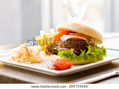 Burger poster. Beef, cheese, tomatoes, onion, cucumber, lettuce cabbage salad and french fries - stock photo