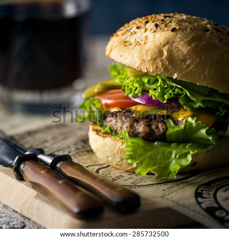 Burger with a beef patty, cheese, fresh lettuce, onion and tomato on a fresh bun with sesame seed standing on brown paper with glass of beer on a wooden background - stock photo