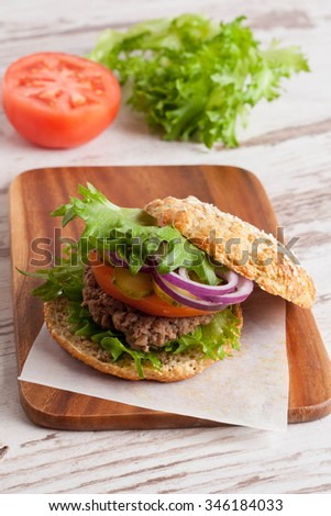 Burger with a vegetarian cutlet and fresh vegetables, close-up, vertical