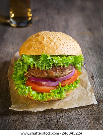Burger with beef cutlet, lettuce, onions and tomato in bun with sesame seed - stock photo