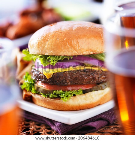 burger with beer glasses and chicken wings - stock photo