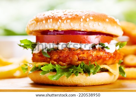 burger with chicken and fries on wooden table - stock photo