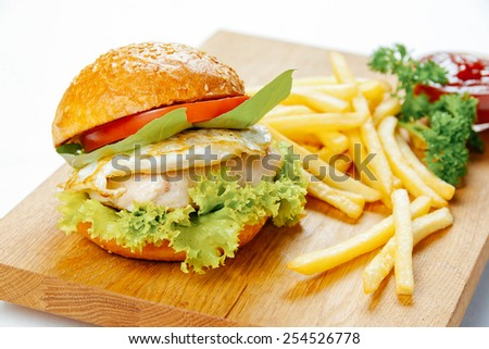 Burger with chicken, fried egg and french fries on a wooden stand - stock photo