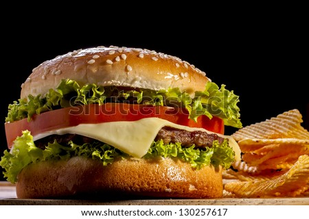 Burger with chips focus on front  in black background.