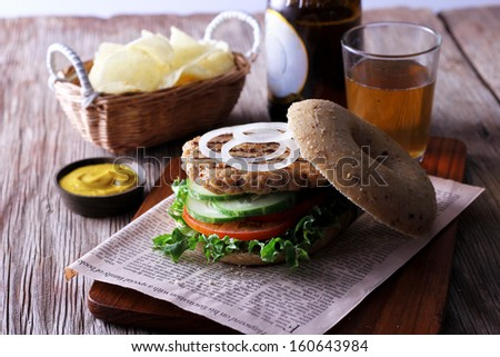 Burger with cucumber and  tomato  on  french  fries background - stock photo