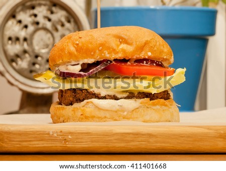 Burger with fresh lettuce, onions, tomato and pickles inside a sesame seed bun. Best fast-food choice with vintage grinder. - stock photo