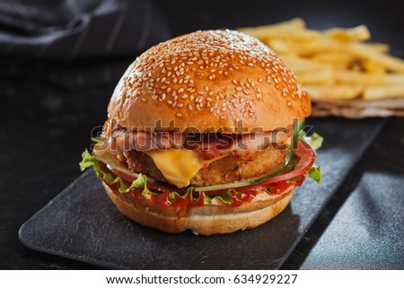 Burger with fried ham, cheese, tomato, cucumber and golden French fries potatoes on background
