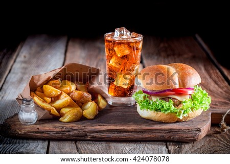 Burger with fries and cold drink on old wooden board - stock photo