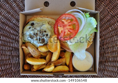 Burger with fries and melted cheese mushrooms. Takeaway food in packaging. - stock photo