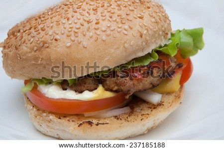 Burger with lettuce, onions, tomato and pickles on a sesame seed bun over white background