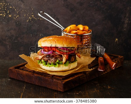 Burger with meat and potato wedges on dark background - stock photo