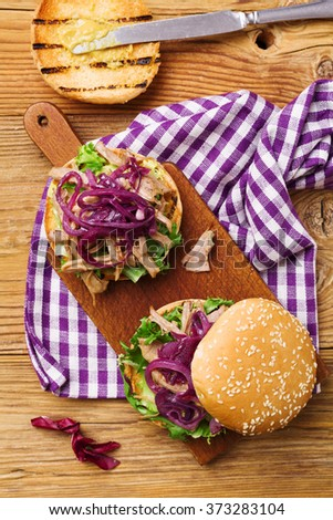 Burger with meat of duck with red onion and lettuce.