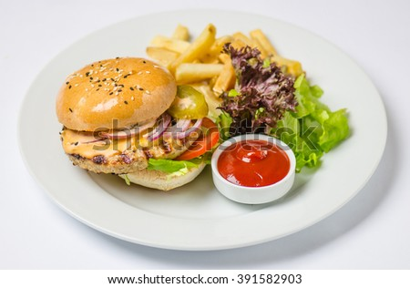 Burger with meat patty , cheese , onions, tomatoes , pickled cucumbers , green salad , potato chips and sauce . Close-up in white plate on a white background.