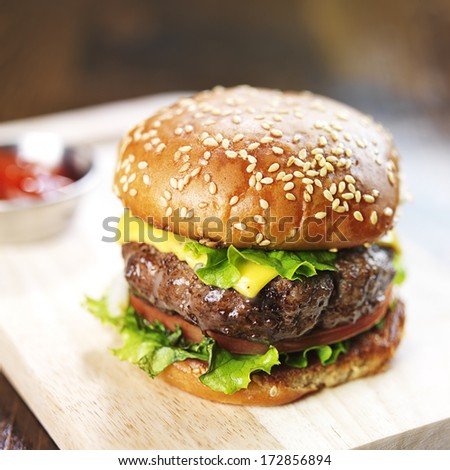 burger with sesame bun and melted cheese close up - stock photo