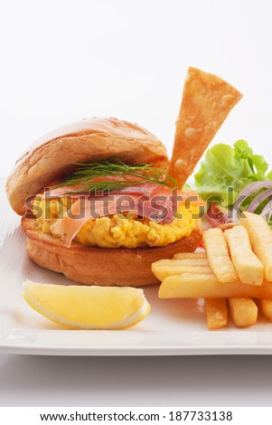 burger with smoked salmon and scrambled egg served with french fried. - stock photo
