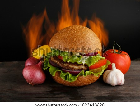 burger with vegetables on wooden table on fire background