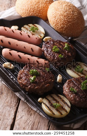 burgers and sausages with vegetables on a grill pan closeup. Vertical - stock photo