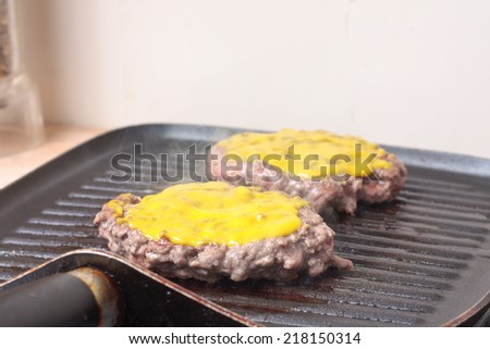 Burgers cooking on a grill-pan with mustard on top - stock photo