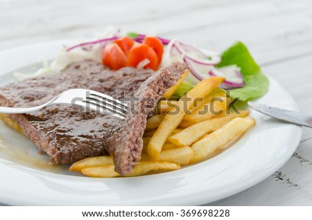 Burgers fried and served with potato and salads on a plate