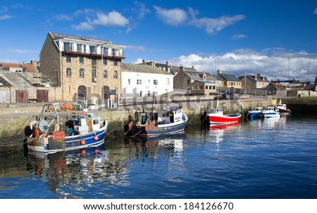 BURGHEAD, SCOTLAND - MARCH 1, 2014: Fishing boats in Burghead Harbour, March 1 2014. Town was built between 1805 and 1809 on the site of a Pictish fort. - stock photo