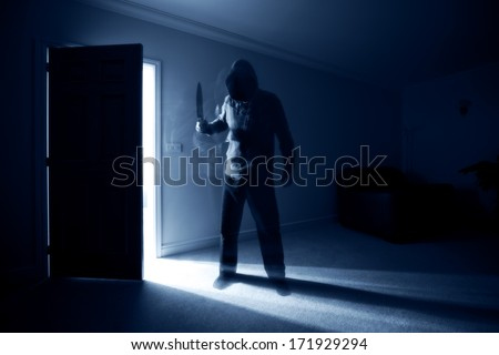 Burglar breaking into a house and threatening with a knife - stock photo