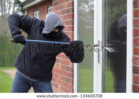 Burglar breaking into a house window with a crowbar - stock photo