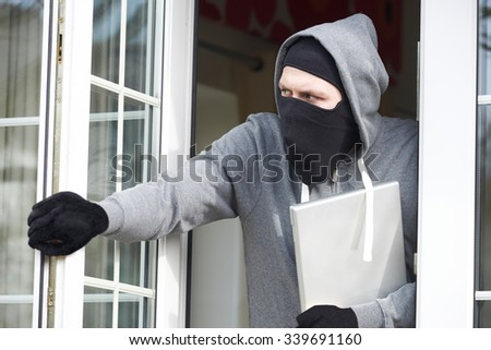 Burglar Breaking Into House And Stealing Laptop Computer - stock photo