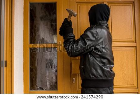 Burglar destroying a front door - stock photo