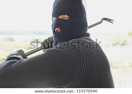 Burglar holding a crowbar and winding up while being in a house - stock photo