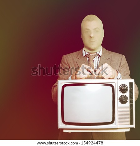 Burglar in a stocking mask and suit stealing an old retro television set as he tries to slip quietly away without being detected during a breaking and entry house robbery - stock photo