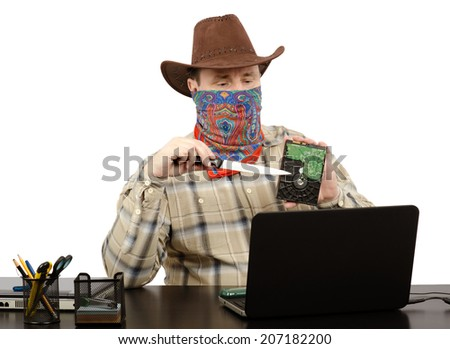 Burglar in cowboy clothes holding knife and hard disk on front of laptop screen - stock photo