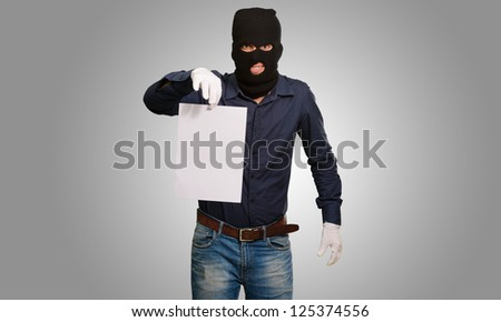 Burglar In Face Mask On Gray Background