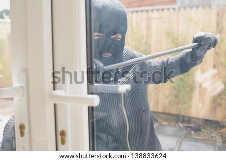 Burglar in garden opening the door with a crowbar - stock photo