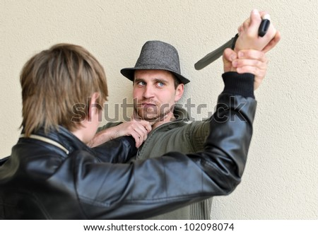 Burglar is trying to kill man by knife. - stock photo