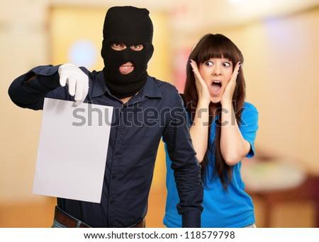 Burglar Man Holding Paper In Front Scared Woman, Indoor - stock photo