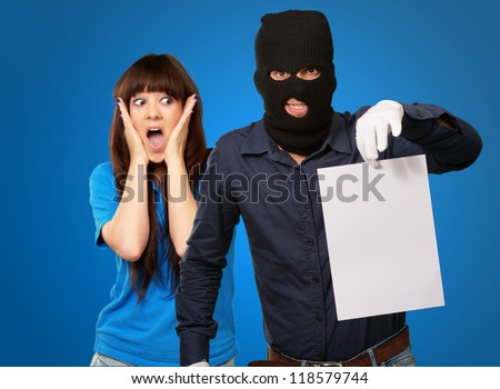 Burglar Man Holding Paper In Front Scared Woman Isolated On Blue Background - stock photo