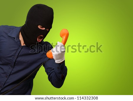Burglar Man Holding Telephone On Green Background - stock photo