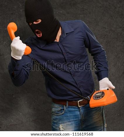 Burglar Man Holding Telephone On Wall - stock photo