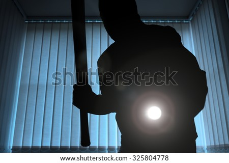 Burglar or intruder inside of a house or office with flashlight and baseball bat - stock photo