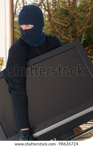 Burglar steals television - stock photo