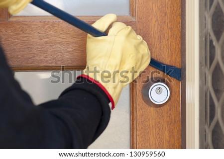 Burglar, thief  with gloves, holding crowbar breaking into home, unlock door, copy space. - stock photo